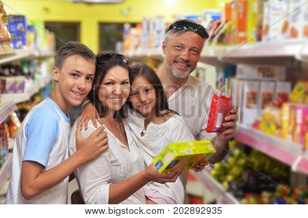 happy family standing in store and choosing dairy products