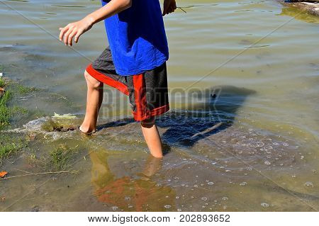Young unidentified boy wades through the muddy water of a slough