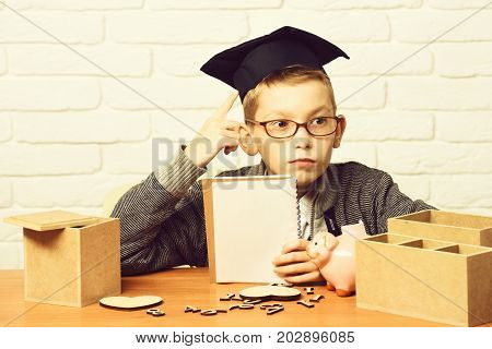young cute pupil boy in grey sweater and glasses sitting at desk with copybook in hand wooden numbers pink piggy pig bank in graduation cap in classroom on white brick wall background