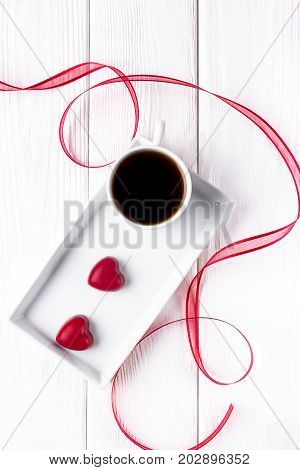 Black coffee in a white cup and two red hearts candy on a white wooden background. Happy Valentine's Day