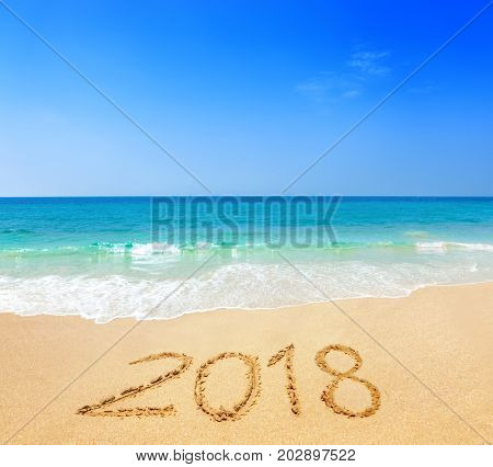 2018 written on sandy beach