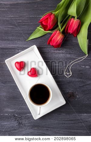 Black coffee in a white cup, two red hearts candy, tulips and heart pendant on a dark wooden background. Happy Valentine's Day