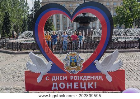Donetsk Ukraine - August 26 2017: Children at the fountain and the symbolism of the self-proclaimed state in the central square of the city
