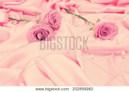 Rose flowers on pink satin fabric with bead strand. Romantic vintage background with copy space