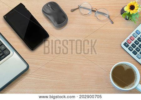 Business office desk wooden table with mouse smartphone glasses flower calculator cup of coffee metaphor to business relaxation modern concept background with copy space top view or flat lay