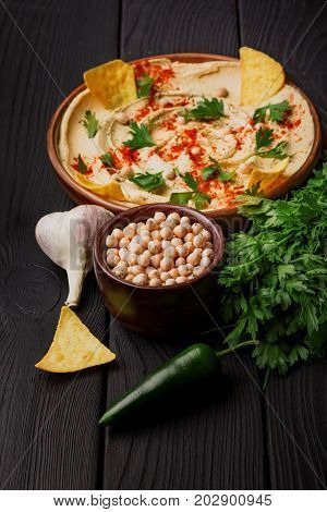Macro picture of a nutritious hummus snack on a black wooden table background. An arabic dish spread over a brown wooden plate. A tasty snack next to a bowl of chickpeas, garlic, greenery, and nacho.