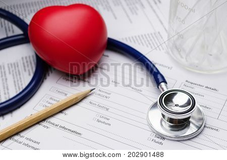 close up stethoscope pencil beaker red heart and patient information form on desk heart healthcare technology medical diagnosis medical report record and history patient concept selective focus