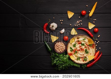A view from above on a classic Middle east appetizer hummus with red hot chili peppers, nachos, parsley, parsley and spices on a wooden table background. Homemade traditional hummus cooking. Copy space.
