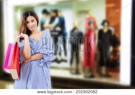 cheerful asian young woman holding shopping bags while standing at the trendy clothes shop in department store shopping mall sale season online payment shopping online lifestyle technology concept
