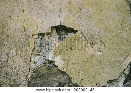 Abstract colorful cement wall texture and background. Texture of old plaster wall of bright yellow. Vintage wallpaper on your desktop. Cracks, scrapes, peeling old paint and plaster