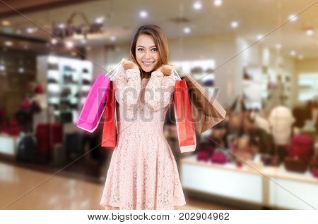 cheerful asian young woman in holding shopping bags while standing at the trendy bag store in department store shopping mall sale season online payment shopping online lifestyle technology concept