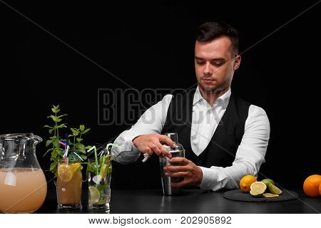 A bartender opens metal shaker, different cocktails with mint and ice, sappy lime, lemons and oranges. Party, cafe, restaurant, night club, concept.