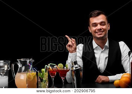 A bar counter with a metal shaker, oranges, lemon, margarita glasses, a bartender shows at something on a black background. Party, night club, cafe, restaurant concept.