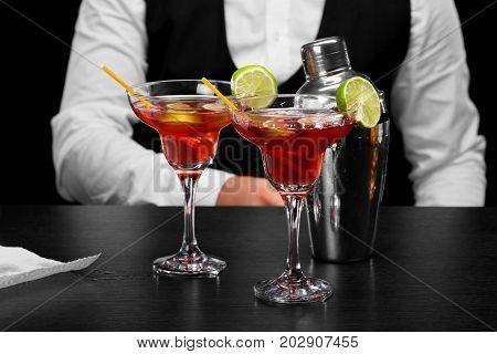 A bar counter with a silver shiny shaker, two margarita glasses, a bartender on a dark blurred background. Party, night club, night out concept.