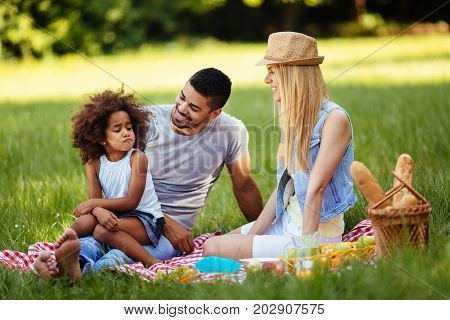 Offended little girl sitting with parents on picnic in nature