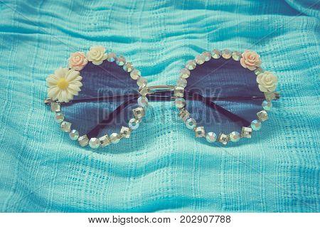 Fashionable eyewear beautifully decorated. Lay on blue fabric floor. Vintage style