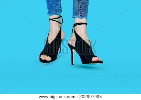 Legs of women wearing high heels black fashion beautifully. Standing on a blue background