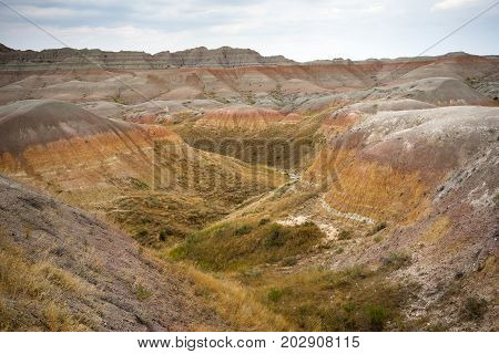 The clouds allow the sun to light rock formations in the South Dakota Badlands