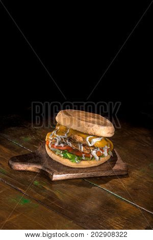 Big delicious hamburger with 2 chicken burgers, melted cheddar, catupiry and tomato on a dark wood background