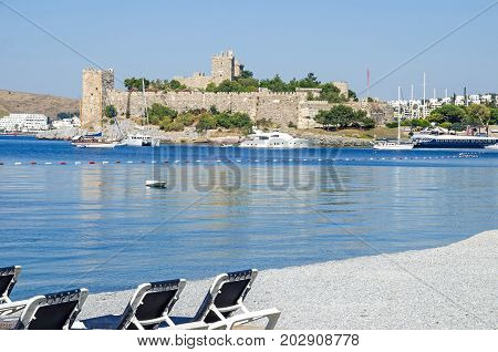 Bodrum Turkey - June 1 2017: View of the Bodrum Castle or St. Peter's Castle from the people less beach with all kind of tourists boats in front.