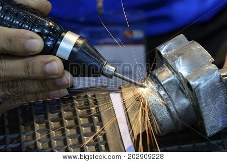 The hand held the mobile welding machine with the sparking light.The welding process for addition material.