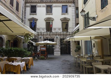 LUCCA, ITALY - AUGUST 15 2015: Small square in Lucca city centre with an outdoor restaurant and the Chamber of Commerce no people
