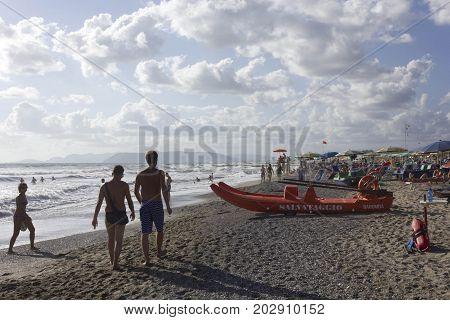 MARINA DI MASSA, ITALY - AUGUSt 17 2015: People on the beach shoreline at sunset light in Versilia Italy