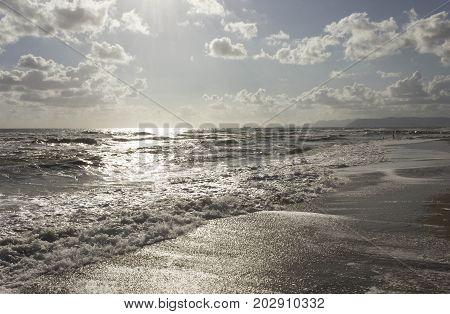 MARINA DI MASSA, ITALY - AUGUST 17 2015: Marina di Massa shoreline at sunset light in a rough seas day Italy