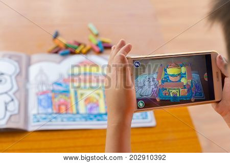 ZhongshanChina-August 29 2017:kid playing Augmented Reality popup paintings of the color filled Taj Mahal via mobile. AR and VR games become more and more popular.