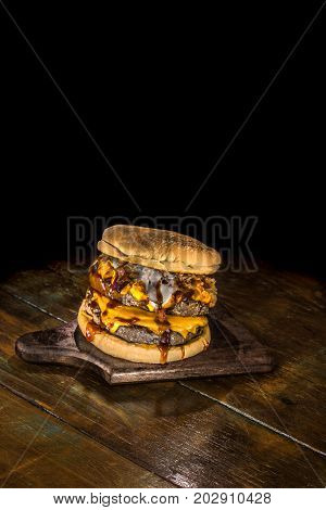 Very big delicious hamburger with 2 burges, cheddar, brie cheese, crunchy onion and barbecue sauce on a dark wood background