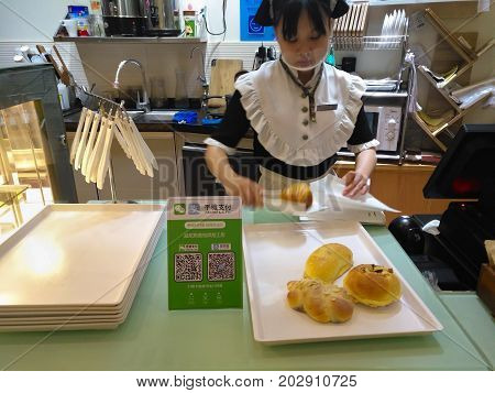 ZhongshanChina-August 26 2017:buying bread with payment via QR code of Wechat or Alipay.QR code for payment and money transfering becomes very common and popular in China.