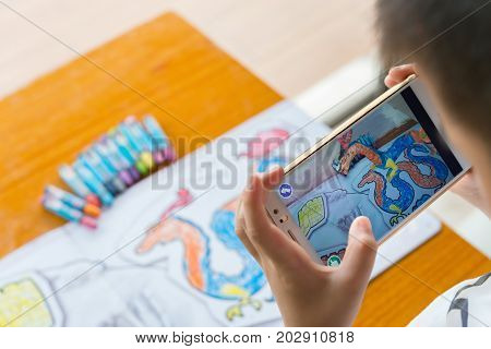 ZhongshanChina-August 19 2017:kid playing Augmented Reality popup paintings of a color filled dragon via mobile. AR and VR games become more and more popular.