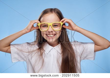 little girl in yellow glasses smiles and laughs, portrait.