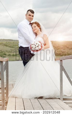 Young Wedding Couple Enjoying Romantic Moments Outside Next To The Pier, On A Summer Meadow.