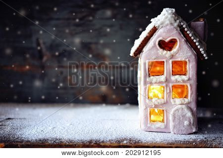 Magical winter christmas picture. Gingerbread house with pink icing with light glimming in the windows under snow falling.