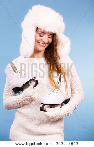 Woman with ice skates getting ready for ice skating. Winter sport activity. Smiling girl wearing warm clothing sweater and fur cap on blue studio shot