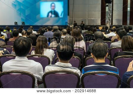 Speakers on the stage with Rear view of Audience in the conference hall or seminar meeting business and education about investment concept