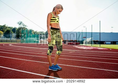 Young sporty woman sprinter athlete in sportswear resting after run on stadium track. Red treadmill in sport field.