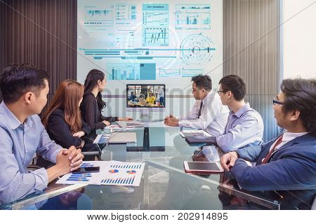 Group of asian Business team having video conference with their manager via monitor display in the modern conference room Business people meeting concept