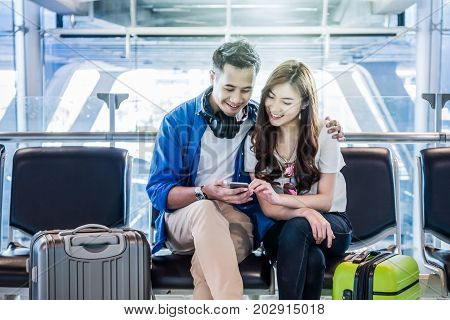 Happiness Asian couple traveler with suitcases using the smart phone in modern an airport travel and transportation with technology concept.