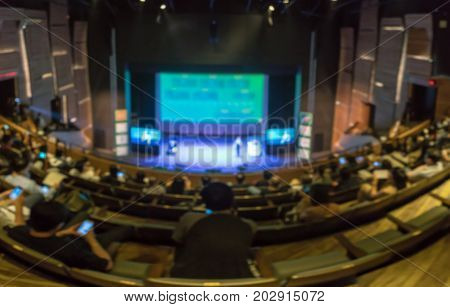 Abstract blurred photo panorama of conference hall or seminar room with attende background in with low light situation business and education concept