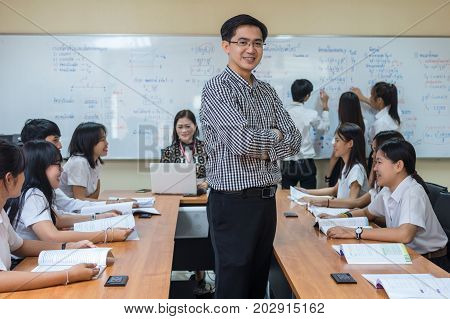 Portrait of Asian teacher standing when Giving Lesson to group of College Students in the classroom University education concept