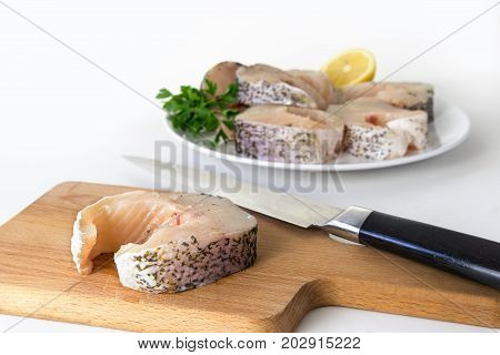 preparing northern pike steaks fresh raw fish piece and knife on a cutting board finished steaks on a plate blurry in the bright background selected focus narrow depth of field