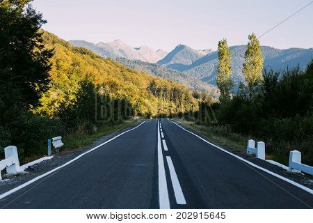 Beautiful road going away into distance with amazing highway far away with mountains and forest and sun light sunset or sunrise inspiring and mesmerizing