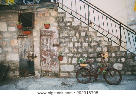 Side of building and stairs made from old bricks and wooden doors decorated with plants hanging old painted vintage bike concept provence design lifestyle rustic