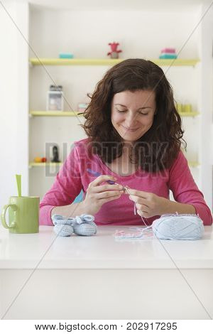 young woman working at her textile studio and creating baby bootees