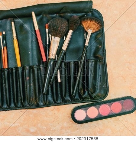 Set of professional colorful cosmetics and makeup brushes for visage. image with toning