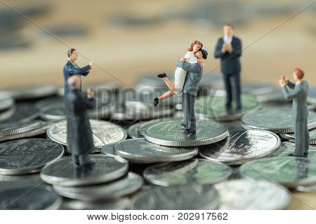 Miniature people couple standing on top stack of coins and other clapping as success love life concept.