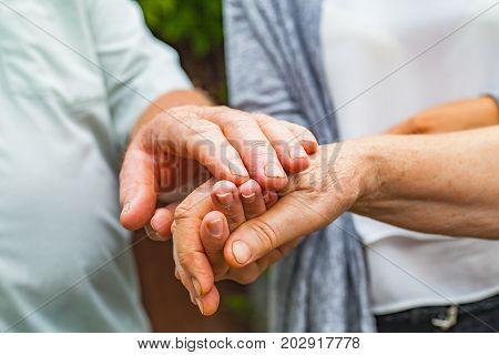 Close up caregiver holding old couple's trembling hands Parkinson disease