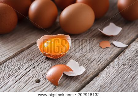 Fresh chicken eggs background, with cracked eggshell and yellow yolk on rustic wood table. Closeup, selective focus